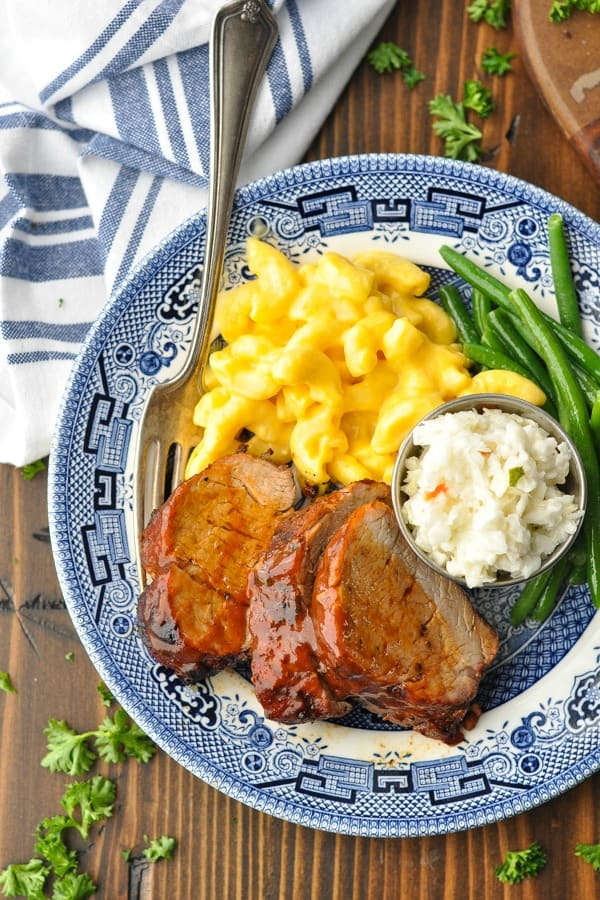 Close overhead shot of grilled pork tenderloin on a plate with mac and cheese green beans and coleslaw