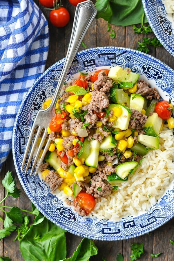 Close overhead shot of ground beef in a bowl with rice and corn zucchini and tomatotes
