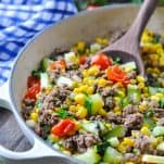 Side shot of a wooden spoon in a skillet with ground beef and mixed summer vegetables