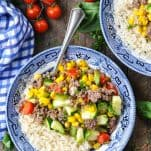 Overhead shot of ground beef with corn zucchini and tomatoes in a bowl with rice