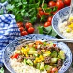Front shot of a bowl of ground beef with rice corn zucchini and tomatoes on a wooden table