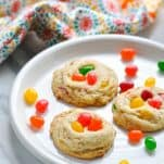Front shot of three jelly bean cookies on a white plate with jelly beans surrounding