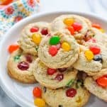 Plate piled high with jelly bean cookies on a white marble surface