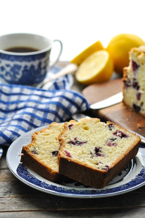 Front shot of two slices of blueberry bread on a plate with fresh lemons in the background