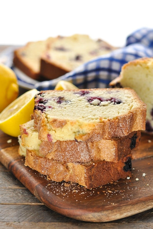 Stack of slices of lemon blueberry bread on a wooden board