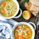 Overhead shot of easy lemon chicken soup with orzo pasta in two white bowls