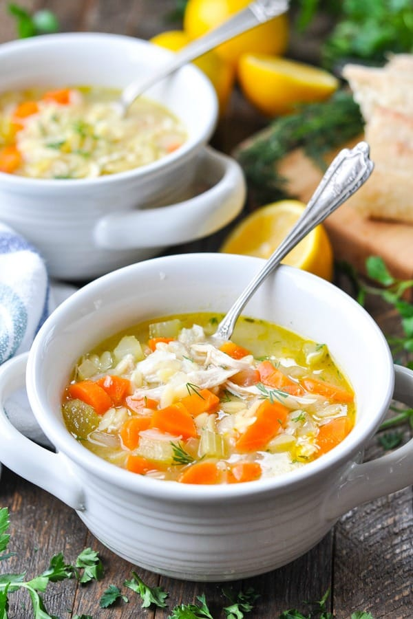 Front shot of a spoon in a bowl of lemon chicken soup with orzo