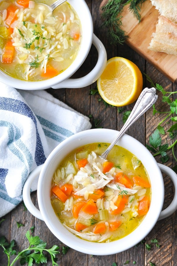 Overhead shot of two bowls of lemon chicken soup with orzo on a wooden table with a side of bread