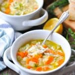 Front shot of two bowls of lemon chicken soup with a baguette in the background