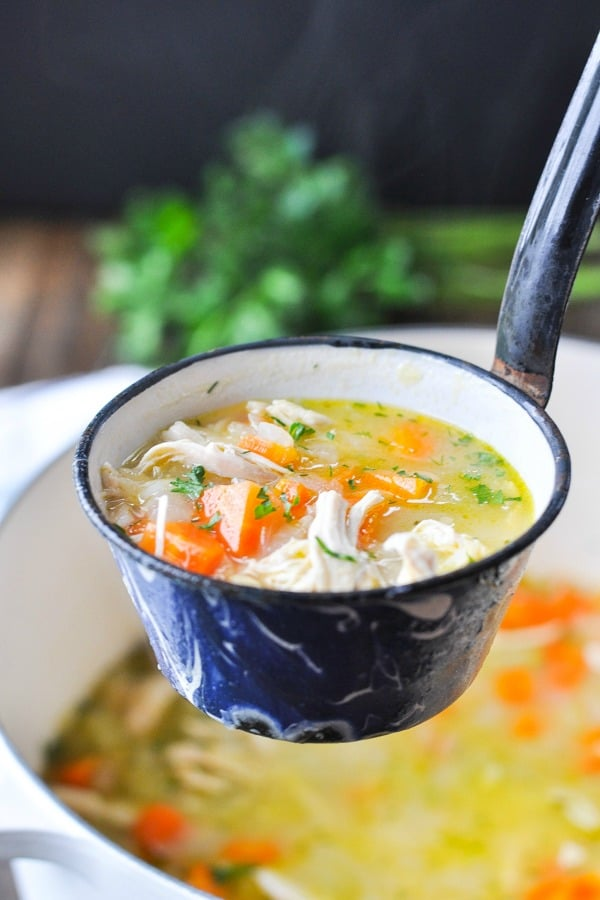 Front shot of lemon chicken soup with orzo in a ladle