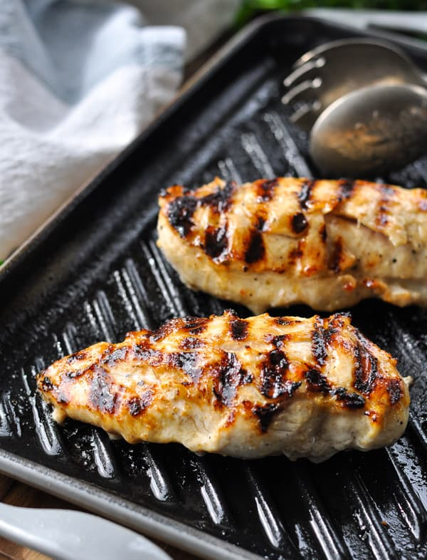 Two Italian dressing chicken breasts on a grill