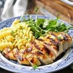 Front shot of grilled chicken breast on a plate with pasta and salad