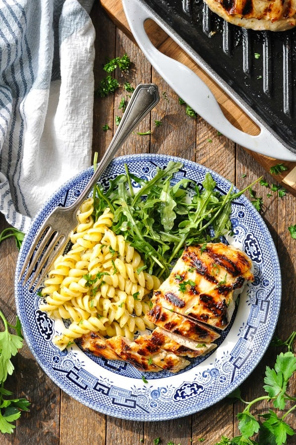 Overhead shot of grilled marinated italian chicken breast on a plate on a wooden table