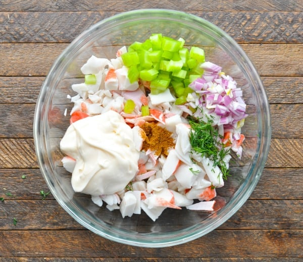 Ingredients for seafood salad in a large glass mixing bowl