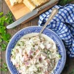 Overhead shot of a bowl of cold crab salad on a wooden table with a side of bread