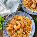 Overhead shot of a bowl of shrimp and sausage pasta on a wooden table