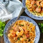 Overhead shot of two bowls of shrimp and sausage pasta with fresh parsley