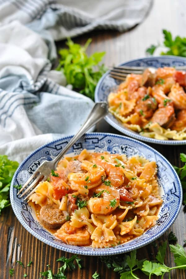 Front shot of two bowls of shrimp and sausage bowtie pasta