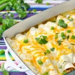 Front angle shot of a pan of creamy white chicken enchiladas garnished with green onions and cilantro