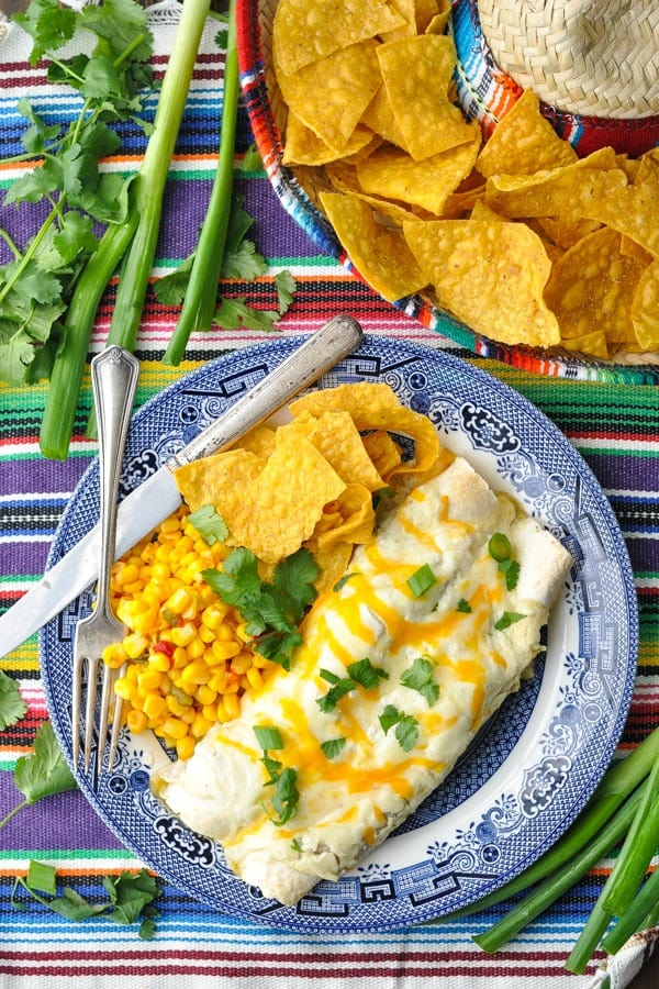 Overhead shot of a plate of creamy white chicken enchiladas on a colorful striped placemat