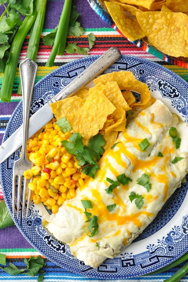 Close overhead shot of two sour cream chicken enchiladas on a plate with a side of tortilla chips and fiesta corn