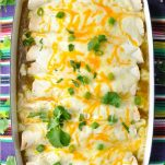 Overhead shot of a pan of sour cream chicken enchiladas with green sauce in a white dish on a striped tablecloth