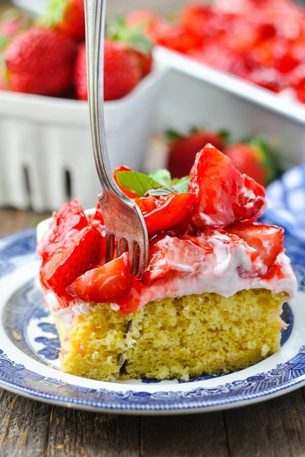 Fresh strawberry cake on a plate with a fork taking a bite