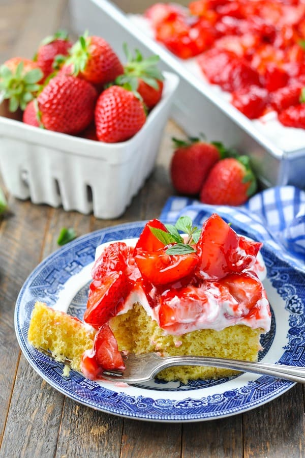 Front shot of a slice of strawberry cake on a blue and white plate with a bite on the fork