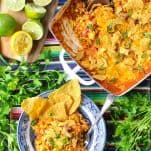 Overhead shot of taco casserole with rice and tortilla chips on a table surrounded by fresh parsley