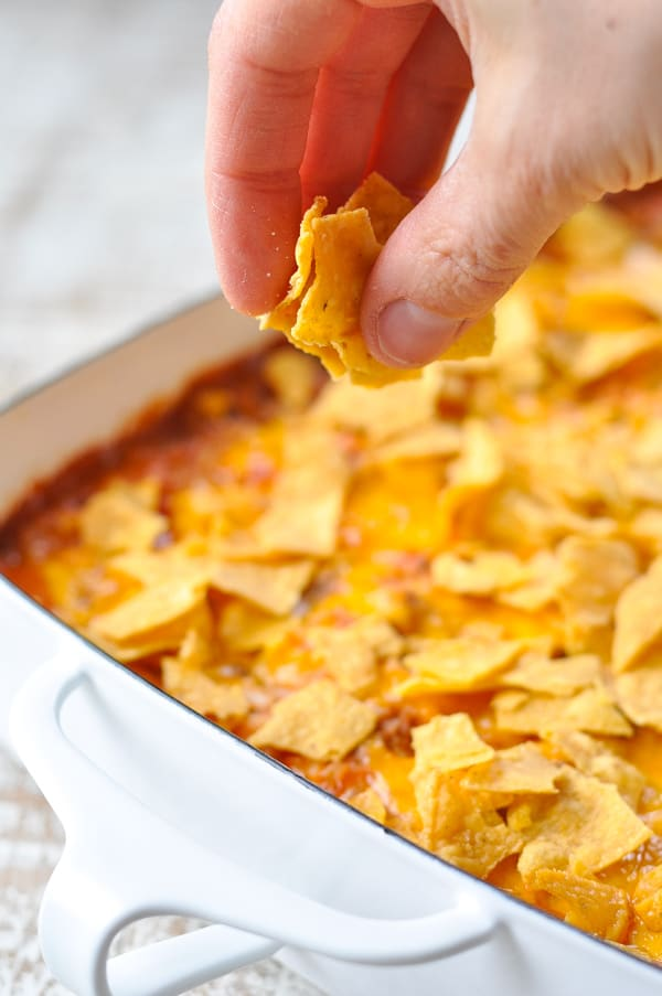 Adding crushed tortilla chips to the top of taco casserole
