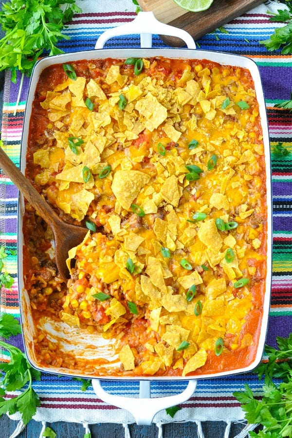 Overhead shot of taco casserole with rice in a white baking dish with a wooden serving spoon