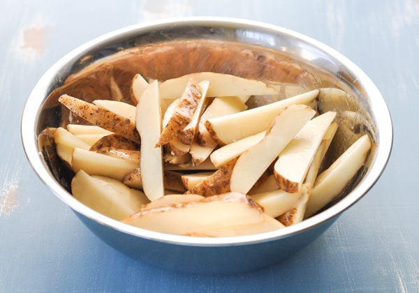 Raw potato wedges in a large mixing bowl