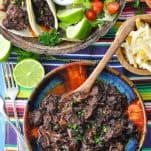 Beef barbacoa in a bowl on a table with Mexican sides