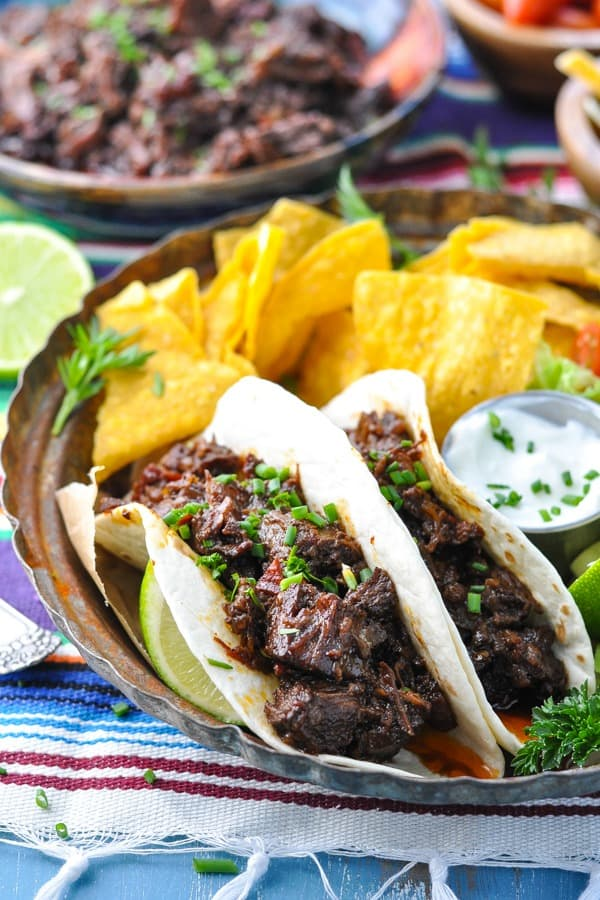 Front shot of beef barbacoa soft tacos on a plate with tortilla chips