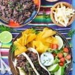 Overhead shot of beef barbacoa on a table with limes and a striped placemat