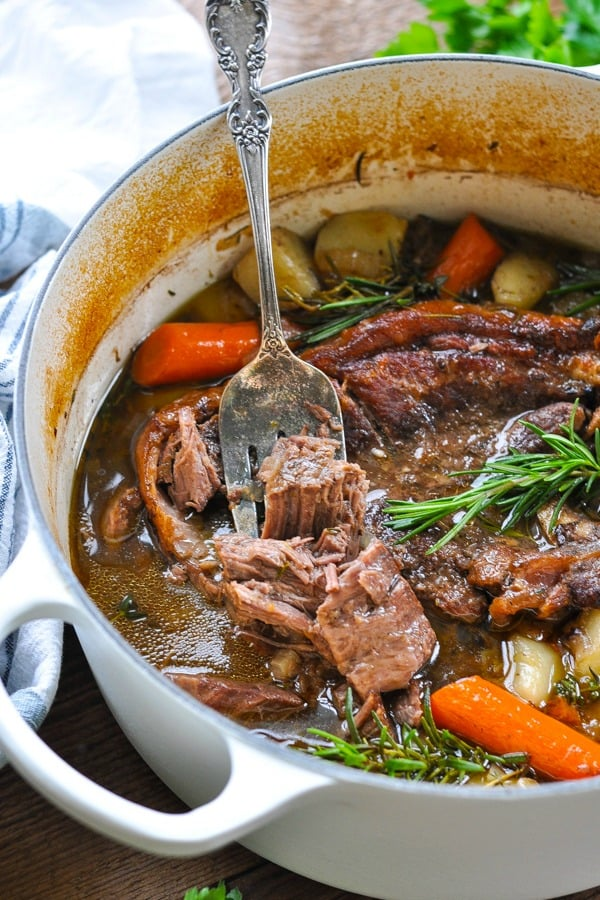 Close up front shot of a white dutch oven full of juicy pot roast with carrots potatoes and gravy