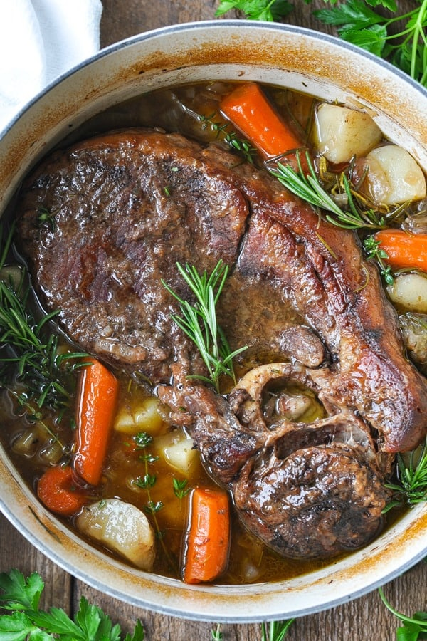 Close overhead shot of dutch oven pot roast with carrots and potatoes