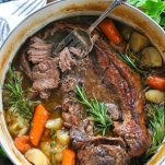 Fork in a dutch oven pot roast with carrots and potatoes in the pot as well