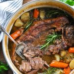 Overhead image of a fork in a dutch oven pot roast with gravy