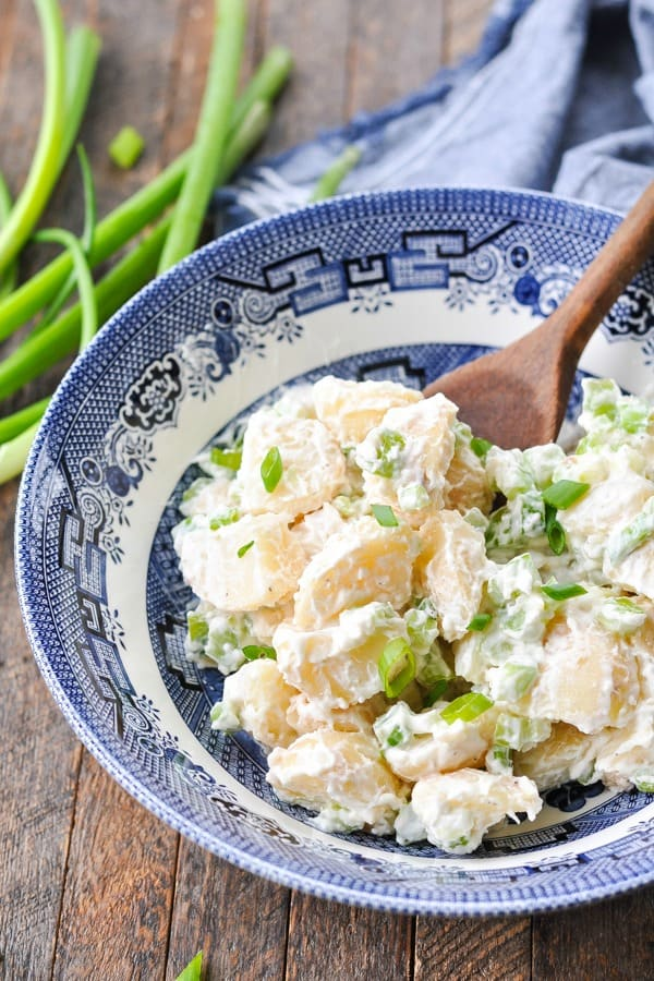 Close front shot of an easy potato salad recipe in a blue and white bowl