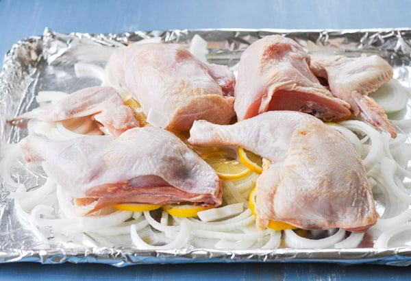 Chicken parts on a rimmed baking sheet before going in the oven