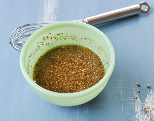 Bowl of greek chicken marinade and seasoning with a whisk
