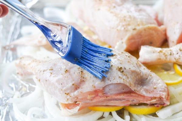 Brushing greek chicken marinade on meat