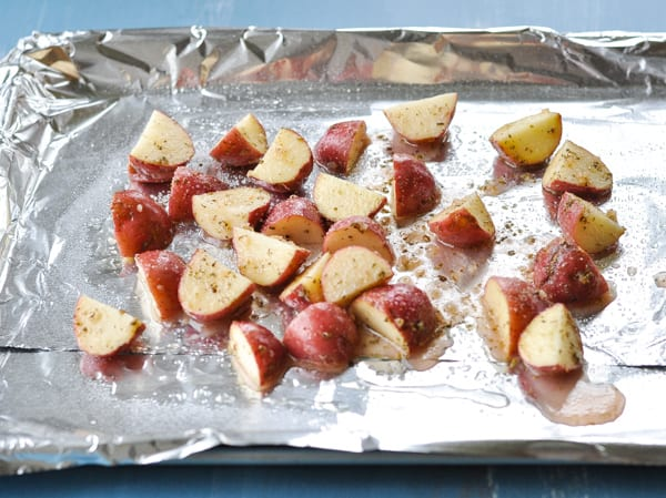 Red potatoes diced and seasoned on a baking sheet before roasting