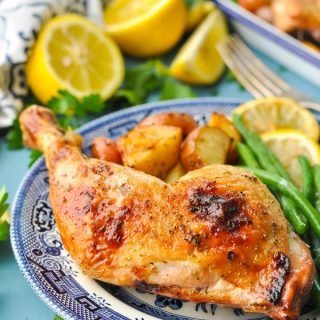 Front shot of Greek chicken and potatoes on a blue and white plate served with green beans