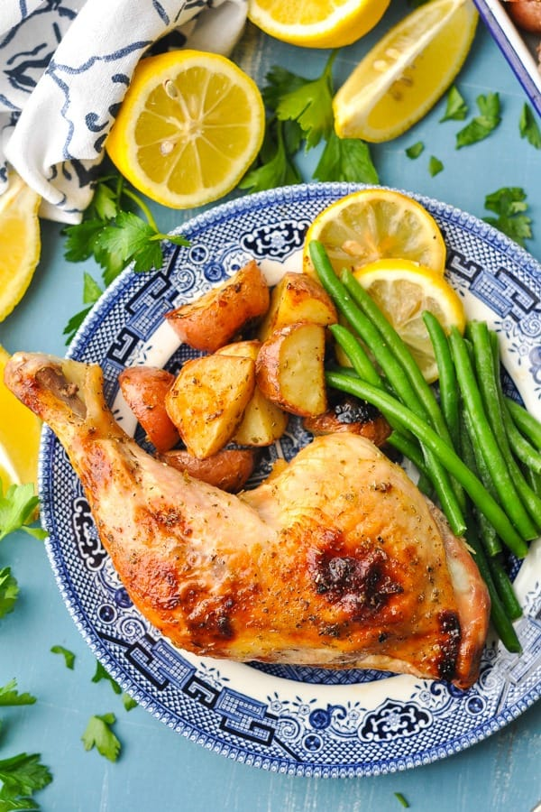 Overhead shot of a plate of Greek chicken and potatoes with green beans and lemons