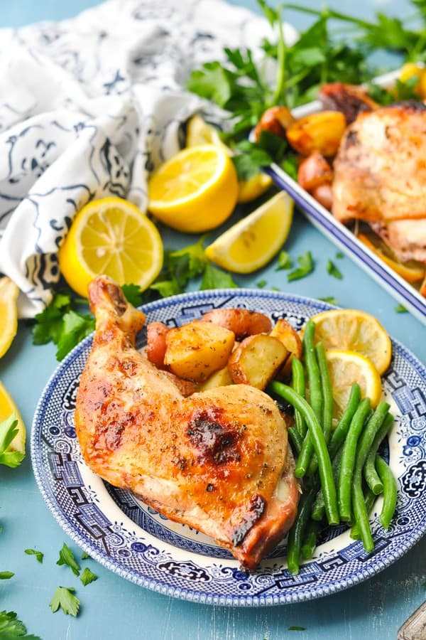 Side shot of greek roasted chicken on a plate with green beans
