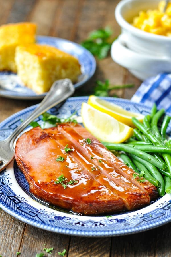 Front shot of glazed ham steak on a plate with green beans and lemon wedges