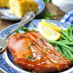 Front shot of glazed ham steak recipe served with green beans and cornbread