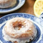 Side shot of a baked lemon donut with glaze on a plate
